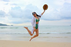 woman jumping while wearing high waisted thong bikini