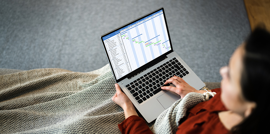 Woman working from home and using timesheet application in her laptop